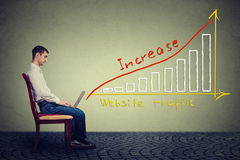 Der junge Mann, der einen Laptop verwendet, hat einen Plan, zum des Websiteverkehrs zu erhöhen Stockfoto