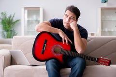Der junge Mann, der Gitarre zu Hause spielend übt Stockfotografie