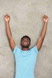 Der junge Mann, der mit den Armen steht, streckte oben zeigen aus lizenzfreies stockbild