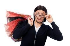 Der junge Mann, der Plastiktaschen lokalisiert auf Weiß hält Stockfoto