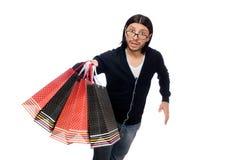 Der junge Mann, der Plastiktaschen lokalisiert auf Weiß hält Stockfotos