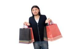 Der junge Mann, der Plastiktaschen lokalisiert auf Weiß hält Lizenzfreie Stockfotografie