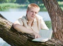 Der junge Mann liest das Buch auf dem Flussufer Stockfotos
