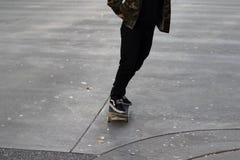 Der junge Mann, der sein Skateboard auf Gummi reitet, befleckte konkrete Fahrbahn Stockfotografie