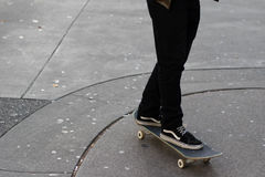 Der junge Mann, der sein Skateboard auf Gummi reitet, befleckte konkrete Fahrbahn Stockfoto