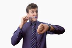 Der junge Mann, der seine Zähne betrachtet putzt auch, an Uhr auf weißem Hintergrund Stockfoto