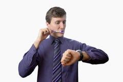 Der junge Mann, der seine Zähne betrachtet putzt auch, an Uhr auf weißem Hintergrund Stockfotografie