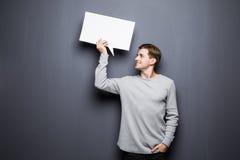 Der junge Mann, der weiße leere Spracheblase mit Raum für Text und Blick an ihm hält, lokalisierte auf grauem Hintergrund Lizenzfreie Stockbilder