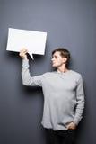 Der junge Mann, der weiße leere Spracheblase mit Raum für Textblick weg hält, lokalisierte auf grauem Hintergrund Lizenzfreie Stockbilder
