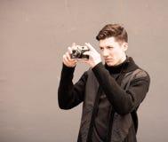 Der junge Mann fotografiert Modell die Weinlesekamera an einer Wand Lizenzfreies Stockfoto