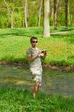 Der junge Mann fotografiert und steht auf der Küste eines Stromes Lizenzfreie Stockbilder