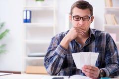 Der junge Mann frustriert an seinem Haus und an Steuerbescheiden lizenzfreie stockbilder