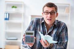Der junge Mann frustriert an seinem Haus und an Steuerbescheiden lizenzfreies stockbild