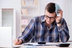 Der junge Mann frustriert an seinem Haus und an Steuerbescheiden stockbilder
