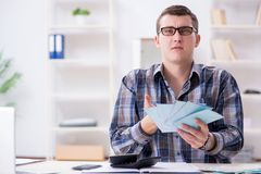 Der junge Mann frustriert an seinem Haus und an Steuerbescheiden stockfotos