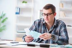 Der junge Mann frustriert an seinem Haus und an Steuerbescheiden stockfoto
