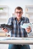 Der junge Mann frustriert an seinem Haus und an Steuerbescheiden stockfotografie