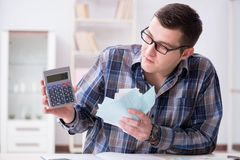 Der junge Mann frustriert an seinem Haus und an Steuerbescheiden lizenzfreie stockfotos