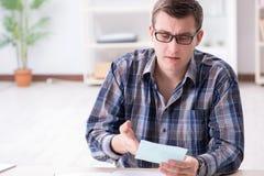 Der junge Mann frustriert an seinem Haus und an Steuerbescheiden stockbild