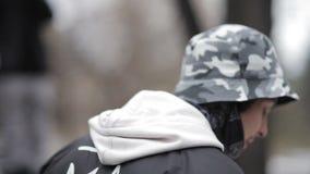 Der junge Mann gleitet auf einem Handlauf auf einem Snowboard stock video
