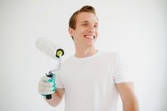 Der junge Mann hält in der Hand die Rolle für die Färbung und lächelt Stockbilder