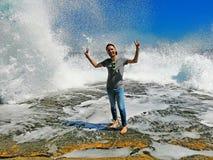 Der junge Mann, der hohe Wellen mit Wasserwellen mit genießt, spritzt lizenzfreies stockbild