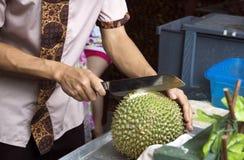 Der junge Mann klärt Durian außerhalb Phuket Stockfotografie