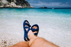 Der junge Mann kreuzte Füße in der blauen Flipflopsandale ein Sonnenbad nehmend auf Seestrand lizenzfreies stockbild
