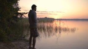 Der junge Mann kurz gesagt trinkt Tee an der Dämmerung auf See stock video