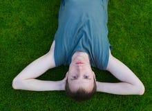 Der junge Mann liegt auf einem Gras Stockbild
