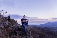 Der junge Mann, der mit auf der Oberseite von Bergen gelegen ist, betrachtet in den Abstand Sonnenuntergang stockfoto