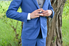 Der junge Mann mit einer Zigarette in einer Hand knöpft eine Jacke Stockbilder