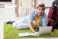 Der junge Mann, der online seins Reise plant lizenzfreie stockbilder