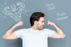 Der junge Mann, der seine Muskeln betrachtet, nach dem Handeln, trainiert in der Turnhalle Lizenzfreies Stockfoto
