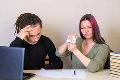 Der junge Mann sitzt durchdacht, das Mädchen zerknittert das Dokument in seinen Händen stockfotos
