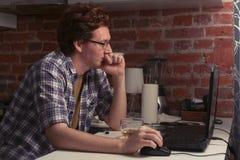 Der junge Mann sitzt an einem Laptop in der Küche und im trinkenden Tee Stockfotos