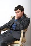Der junge Mann sitzt in einem Stuhl Stockfoto