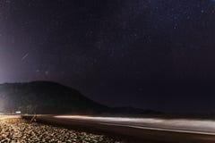 Der junge Mann sitzt unter den Sternen auf dem Strand Lizenzfreie Stockfotografie