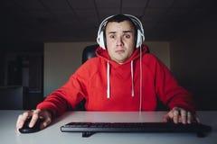 Der junge Mann spielt ein Heimspiel auf seinem Computer Gamerfurcht, die Ihren Computermonitor betrachtet stockfotografie