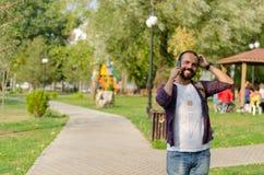 Der junge Mann spricht an seinem Handy am Park lizenzfreies stockfoto