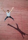 Der junge Mann springt mit Freude Stockbild