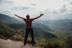 Der junge Mann steht auf einem Felsen und Blicken am Tal Trekking in den Bergen stockfoto