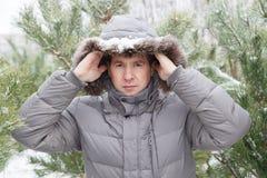 Der junge Mann unter Tannenbäumen in einer Haube Stockbild