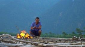 Der junge Mann wärmt sich durch das Feuer auf einem sandigen Strand stock footage