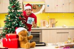 Der junge Mann, der Weihnachten in der Küche feiert lizenzfreie stockfotos