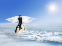 Der Junge mit dem Telefon im Kostüm mit Angel Wings auf einem Felsen Lizenzfreies Stockfoto