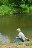 Der Junge mit einem Netz auf der Querneigung von See Lizenzfreie Stockfotos
