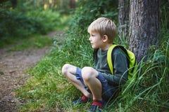 Der Junge, der mit einem Rucksack blond ist, sitzt in einem Wald Stockfoto