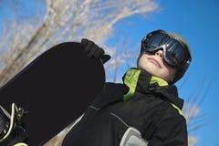 Der Junge mit einem Snowboard im Winter Lizenzfreie Stockbilder