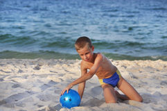 Der Junge mit einer Kugel auf einem Strand Lizenzfreie Stockfotografie